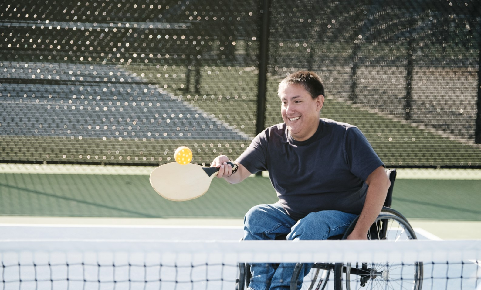Social Care - A young man in a wheelchair playing the game of pickleball