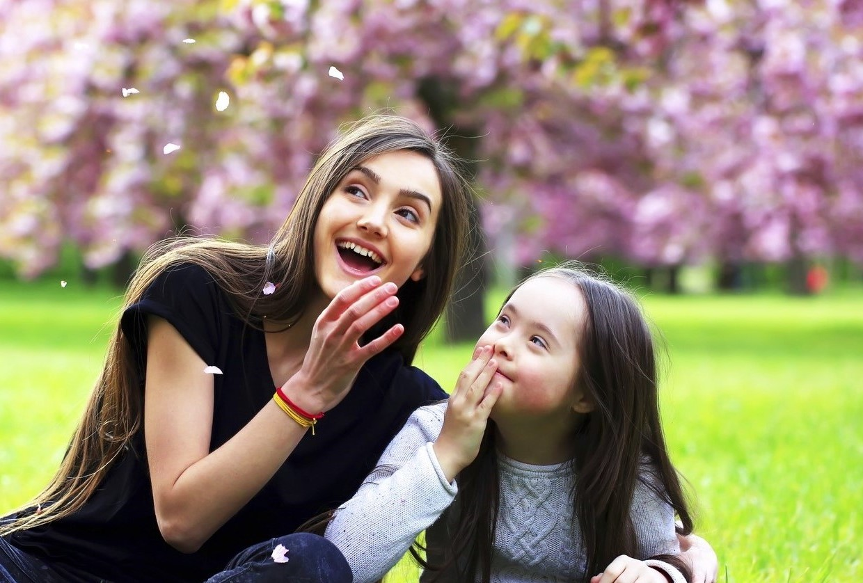 Social Care - Happy support worker with young girl on grass with cherry blossoms